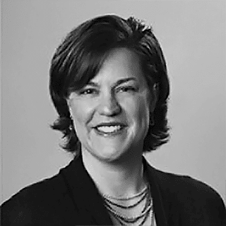 Black and white photo of Giulia Tollis with short dark hair wearing a dark suit jacket and multiple necklaces